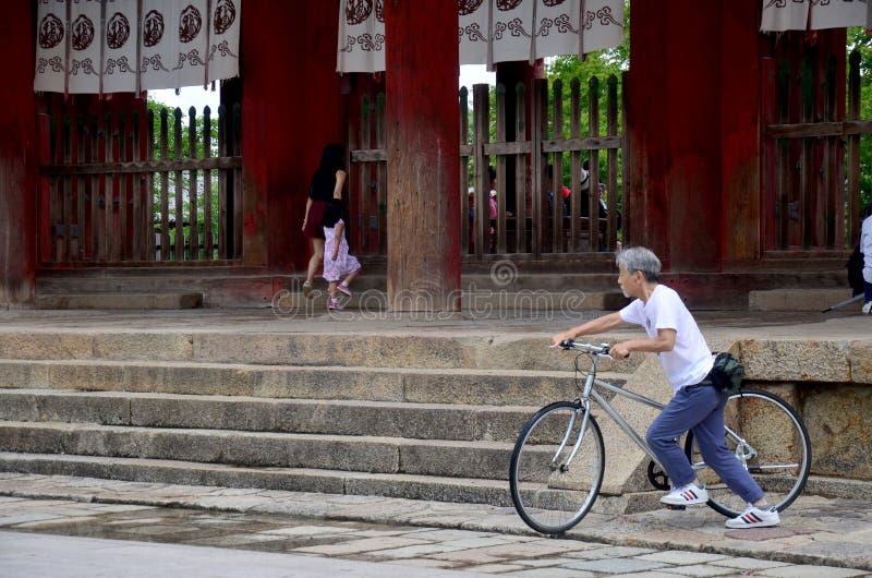 在Todai籍寺庙的日本老人骑马自行车 免版税图库摄影