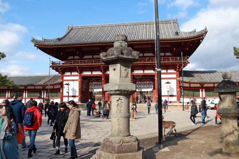 在Todaiji寺庙前面第二个古色古香的木拱道入口的石灯笼  免版税库存照片