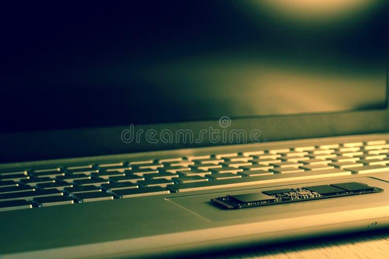 在trackpad的芯片SSD驱动 部分地在锋利 键盘部分地被弄脏,从底部的侧视图 照片usin 免版税库存照片