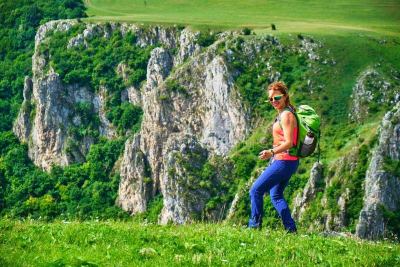 在Tureni/Copaceni峡谷,罗马尼亚上的愉快的女性徒步旅行者,无所事事,仿效一个占士邦姿势,在一个绿色领域 库存图片