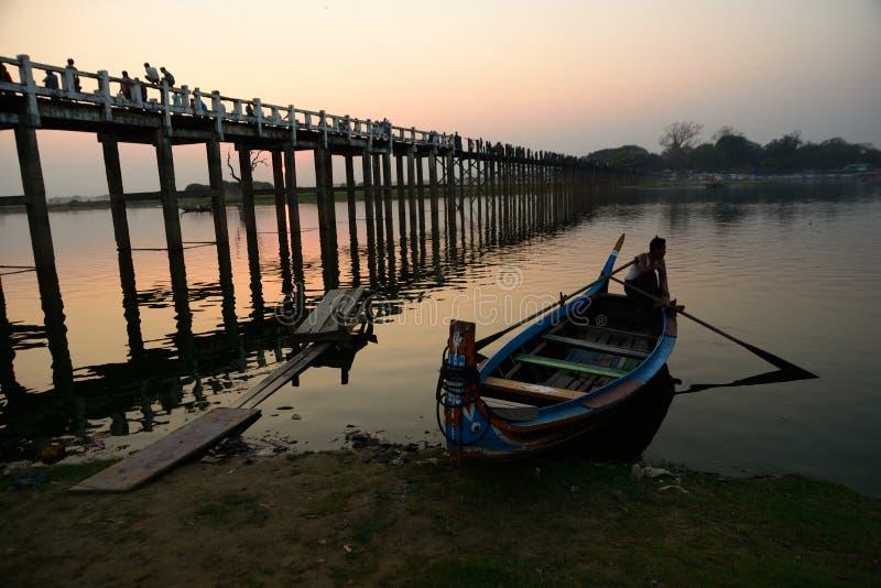 在U Bein桥梁的小船在日落期间 库存图片