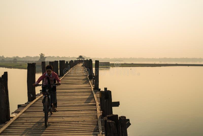 在U Bein桥梁的年轻缅甸骑马自行车 免版税库存照片