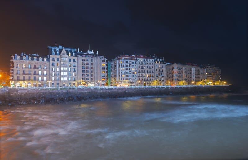 在Urumea河、Cantabrian海和市的大厦的蓝色照明设备Donostia 库存图片