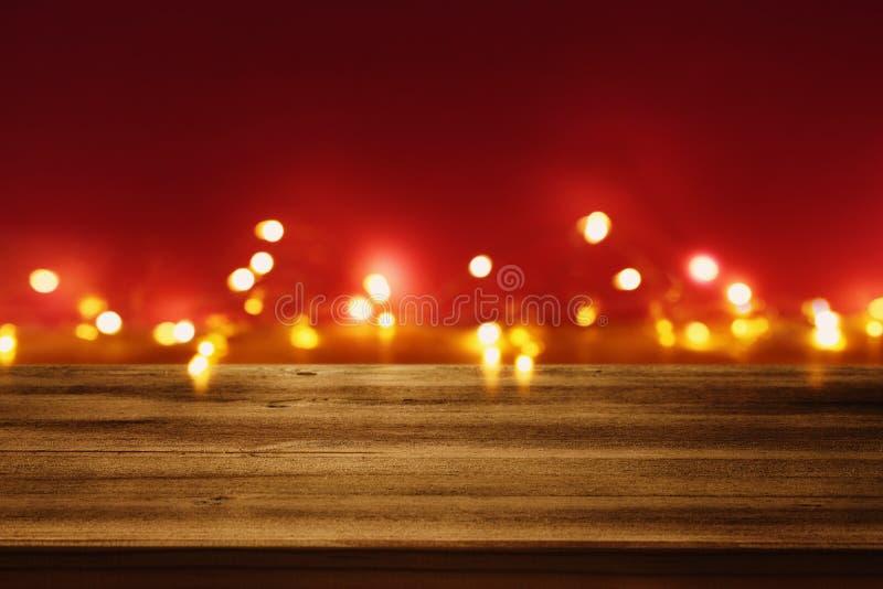 在Valentine'前面的空的土气桌;s天或圣诞节闪烁bokeh背景与金光 库存照片