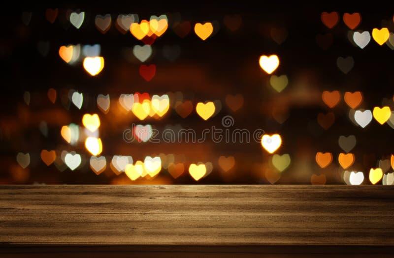 在Valentine& x27前面的空的土气桌; 与许多心脏的s天浪漫闪烁bokeh背景点燃 库存照片
