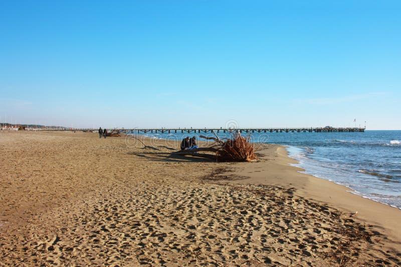 在Versilia沙滩的美好的晴朗的冬日在福尔泰德伊马尔米的 在天际、小的蓝色海和a的码头 库存照片