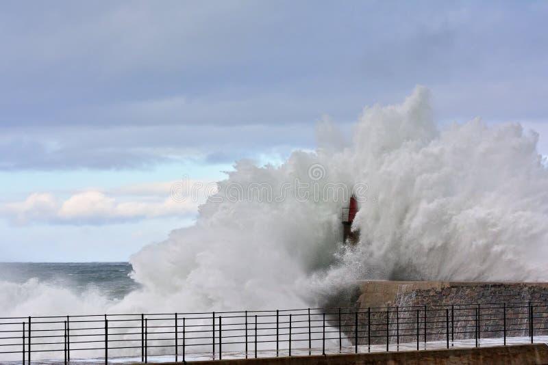 在Viavelez老灯塔和码头的风雨如磐的波浪  免版税库存图片
