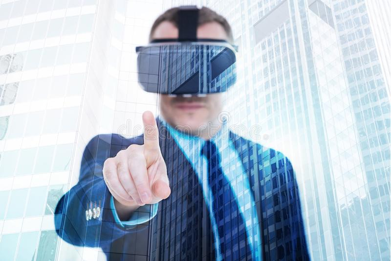 在VR耳机的年轻商人指向与手指的照相机 库存图片