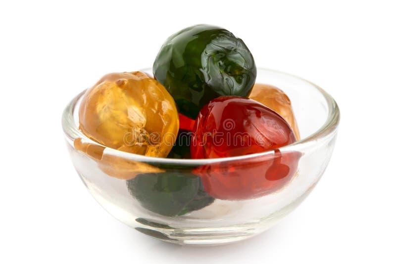 在w隔绝的玻璃碗的红色,绿色和黄色糖渍的樱桃 库存图片