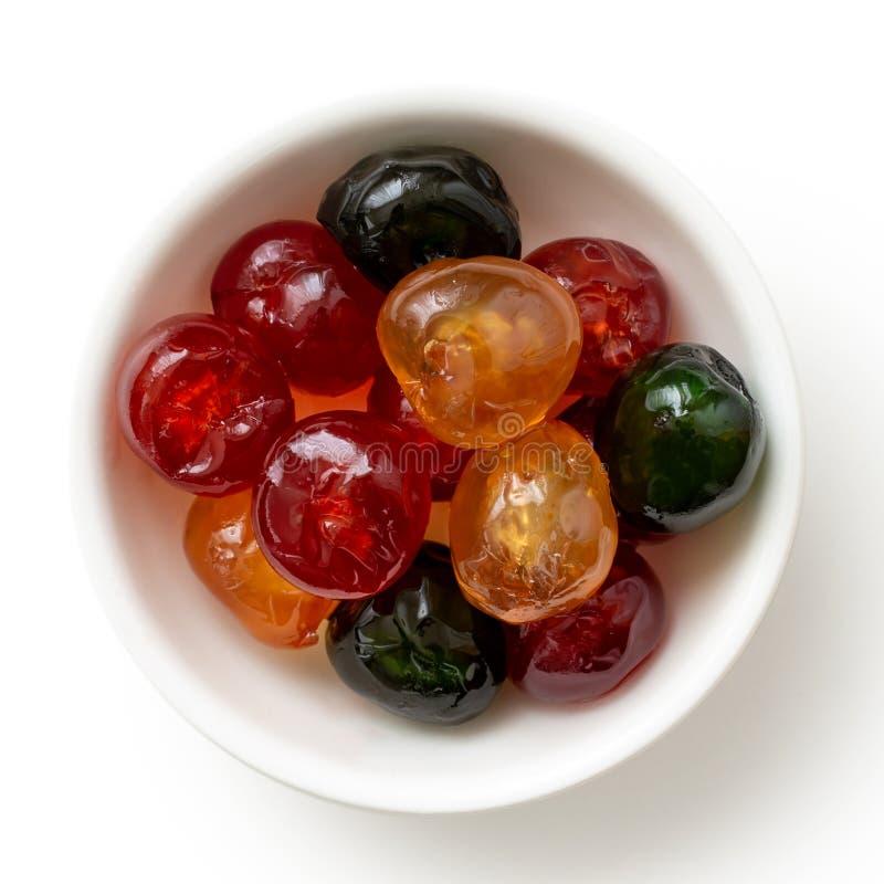 在w隔绝的白色碗的红色,绿色和黄色糖渍的樱桃 免版税库存图片