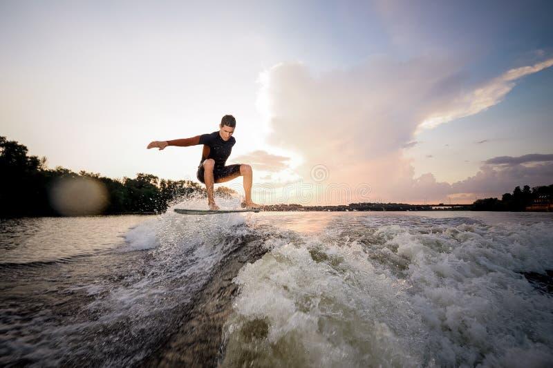 在wakeboard的年轻有吸引力的人骑马在背景o 免版税库存图片