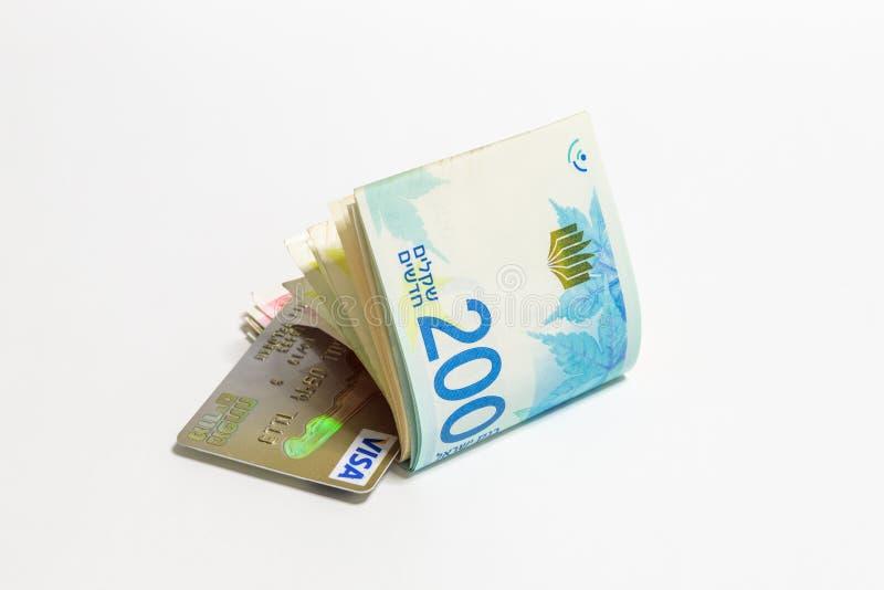 在wh在锡克尔NIS与金子塑料信用卡签证隔绝的以色列金钱堆另外价值新的以色列钞票 图库摄影