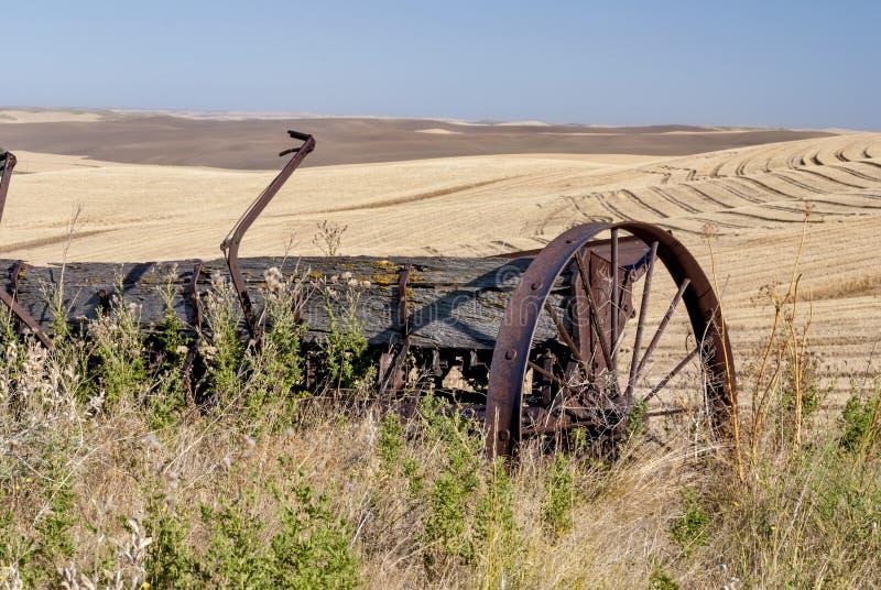 在wheatfields的老被风化的农场设备 免版税库存图片