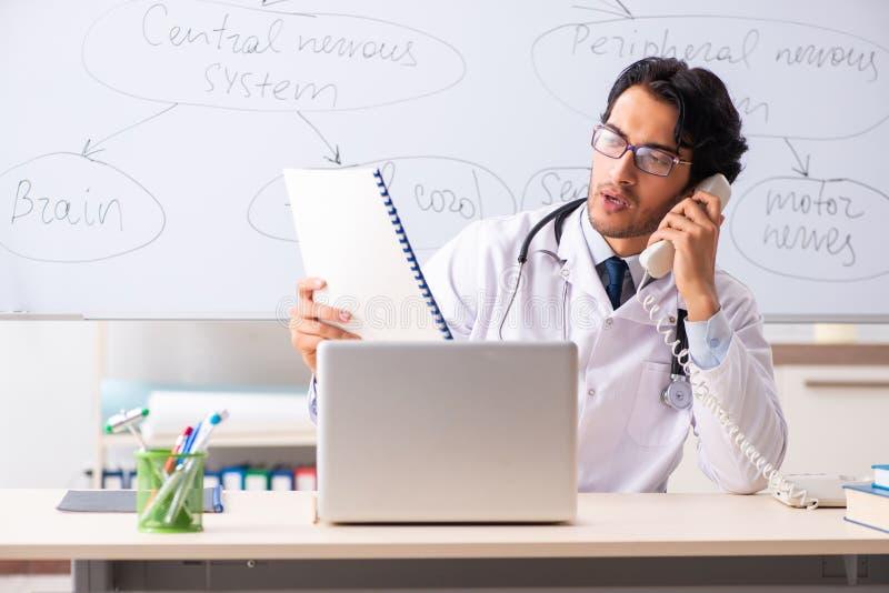 在whiteboard前面的年轻男性医生神经学家 免版税库存照片