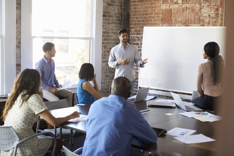 在Whiteboard的商人在激发灵感会议 免版税库存图片