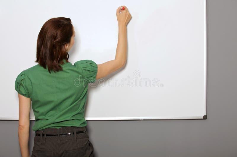 在Whiteboard的女实业家文字在办公室 免版税库存图片