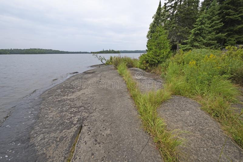 在Wilderness湖岸的古老岩石 图库摄影