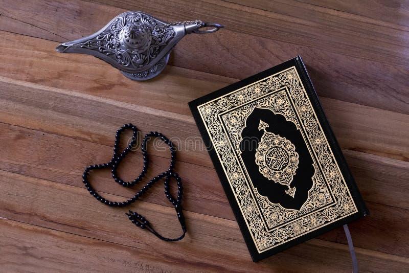 在wodden委员会的伊斯兰教的书古兰经有念珠和aladdin灯的-赖买丹月/Eid概念 图库摄影