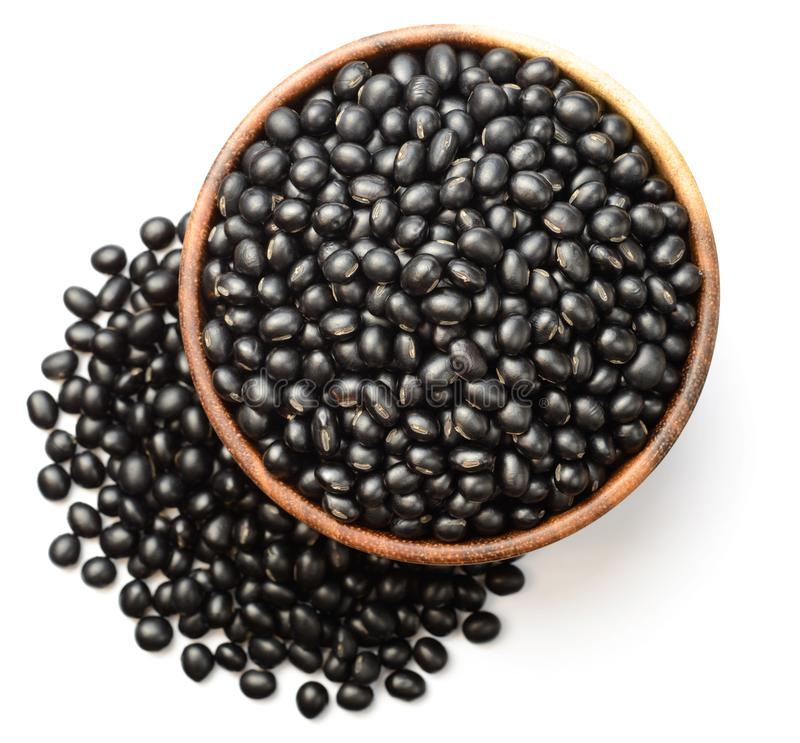 在wooen碗的未煮过的黑豆,隔绝在白色,顶视图 图库摄影