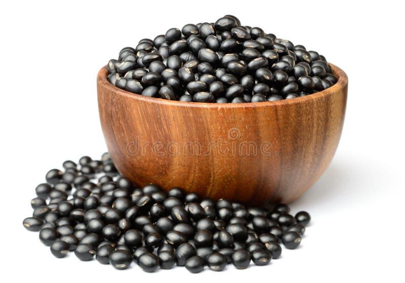 在wooen碗的未煮过的黑豆,隔绝在白色 免版税库存照片
