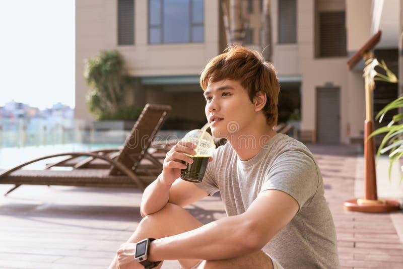 在workou以后的健身亚裔人饮用的菜戒毒所圆滑的人 免版税库存图片