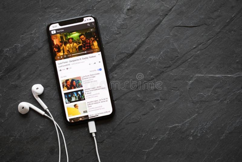 在YouTube图象播放机的IPhone x使用的普遍的歌曲Despacito 免版税库存照片