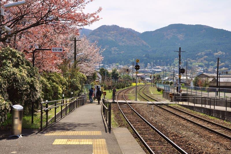 在Yufuin火车站的铁路与樱花和山背景 免版税库存照片