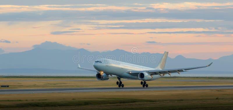 在YVR的航行器着陆在与山的黄昏在背景中 免版税库存照片