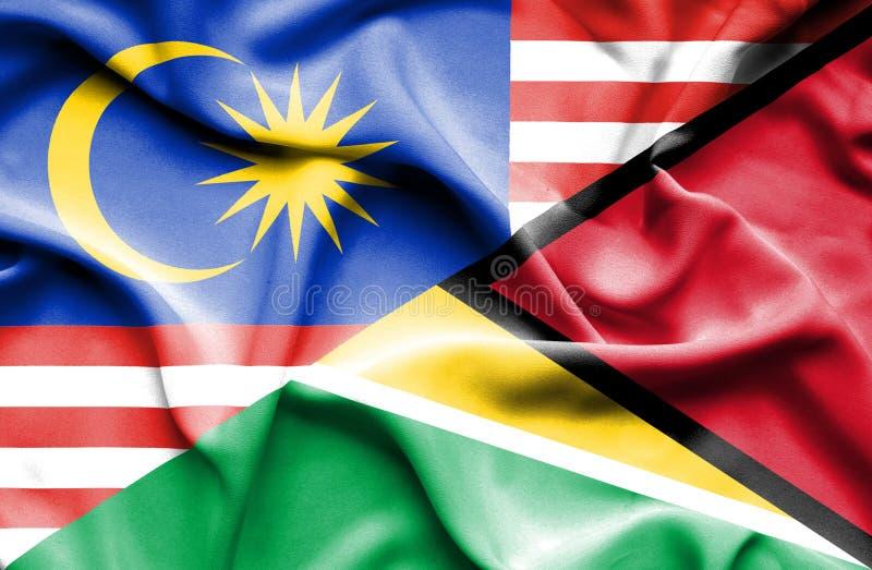 圭亚那和马来西亚的挥动的旗子 库存例证