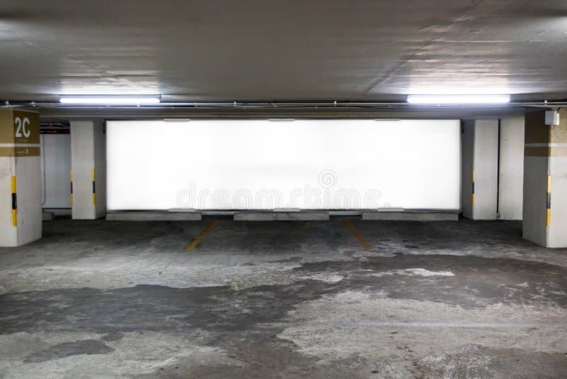 地下与空白的广告牌的停车库内部 在下午的空的空间停车场内部 室内停车场 免版税库存图片