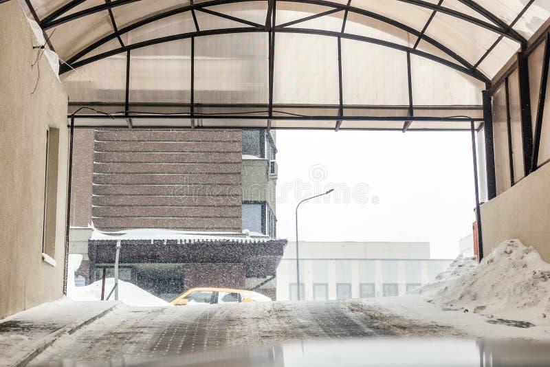 地下停放的出口门 室外的大雪 溜滑路警告 飞雪天气预报 免版税库存照片