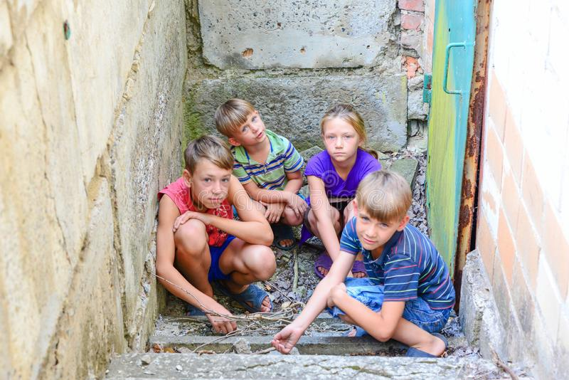 地下室、三个男孩和一个女孩的孩子在铁门附近在步掩藏从外界 之后生产 免版税库存照片