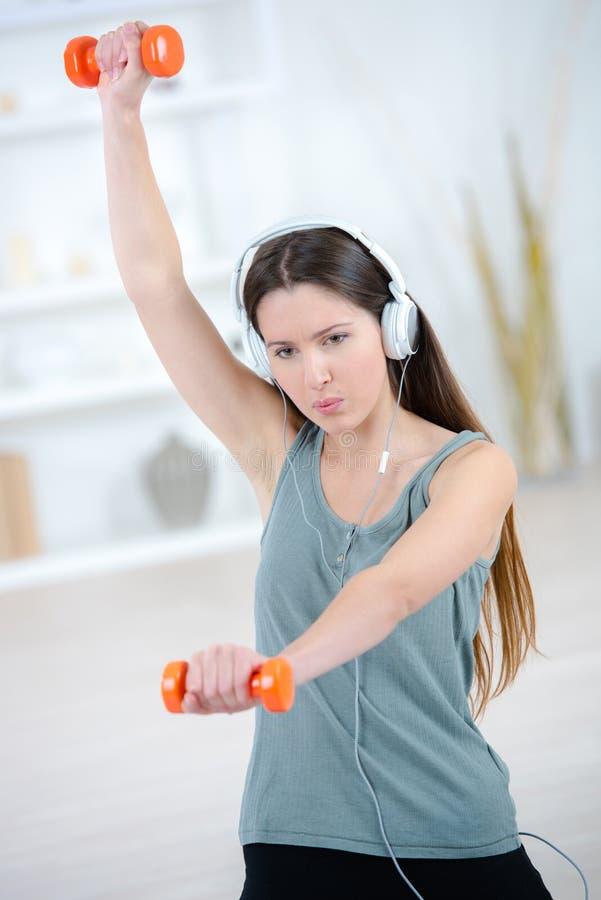 地下室健身房举的重量的年轻美丽的妇女 免版税库存图片