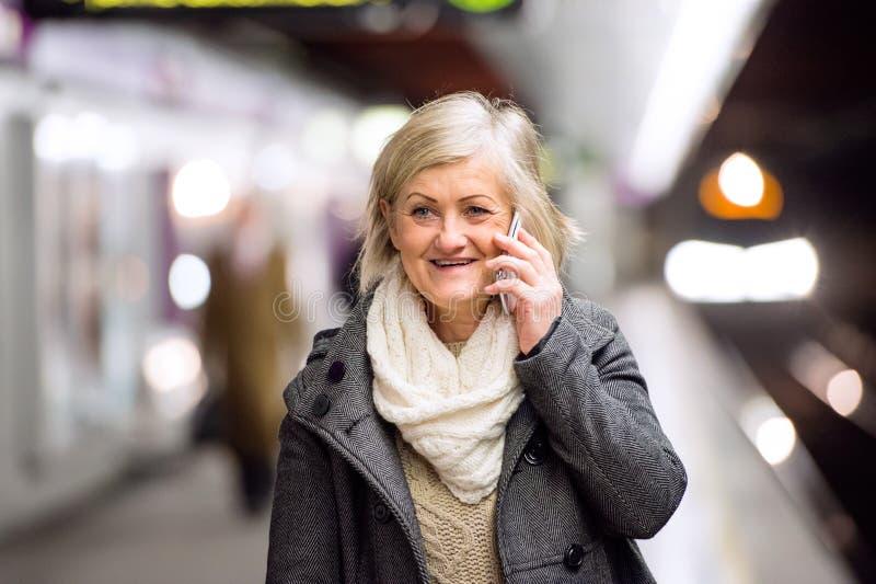 地下平台的资深妇女,谈话在电话 免版税库存图片