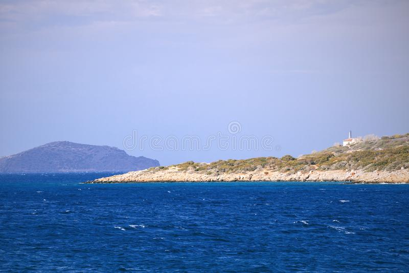 地中海、深大海、岩质小岛与缺乏植被和一些大厦的小希腊海岛 在克利特附近的海岛 免版税库存图片