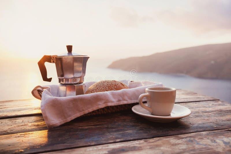 地中海早餐、咖啡和在一张桌上的新鲜面包有在背景的美好的海视图 免版税库存图片