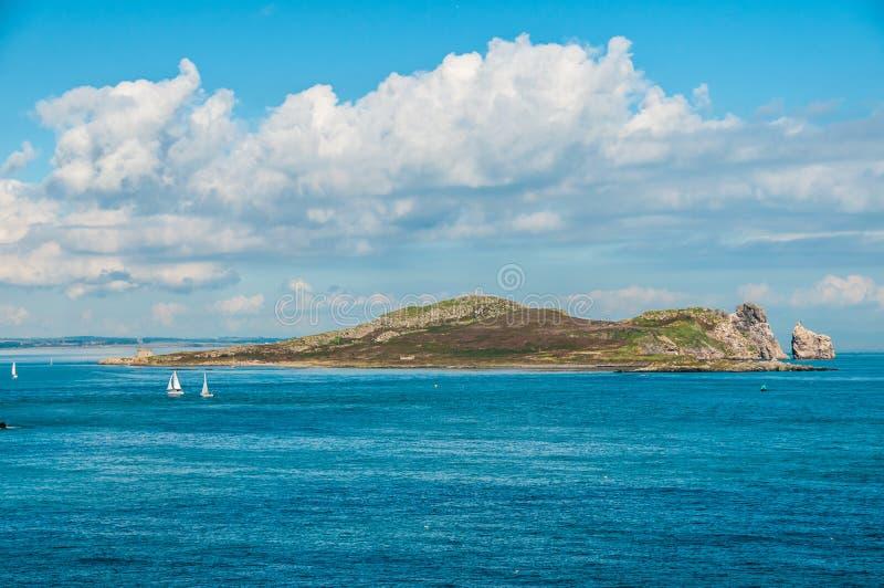 地中海海岛被构筑在与通过的小船的云彩下  免版税库存照片