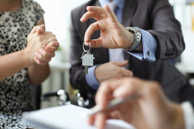 地产商举行反对办公室的房子钥匙的手 免版税库存图片