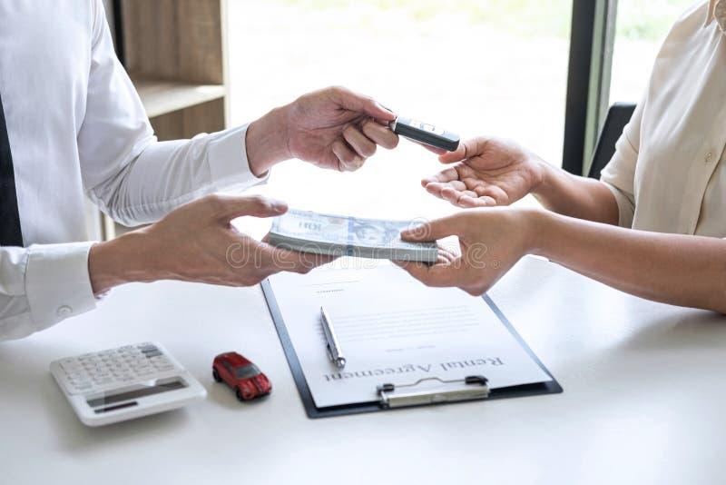 地产商代理经理给妇女客户的新的汽车藏品钥匙在签署出租合同形式和送美元我们以后 图库摄影
