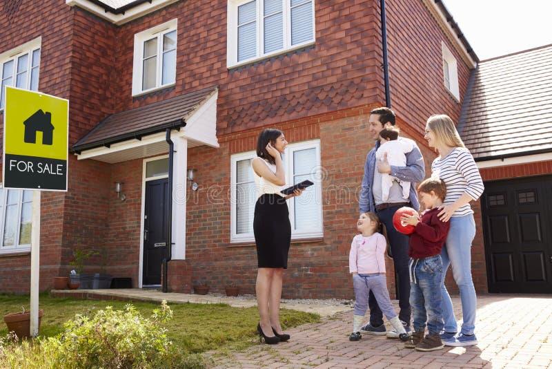 地产商议院外与年轻家庭的待售 免版税库存照片