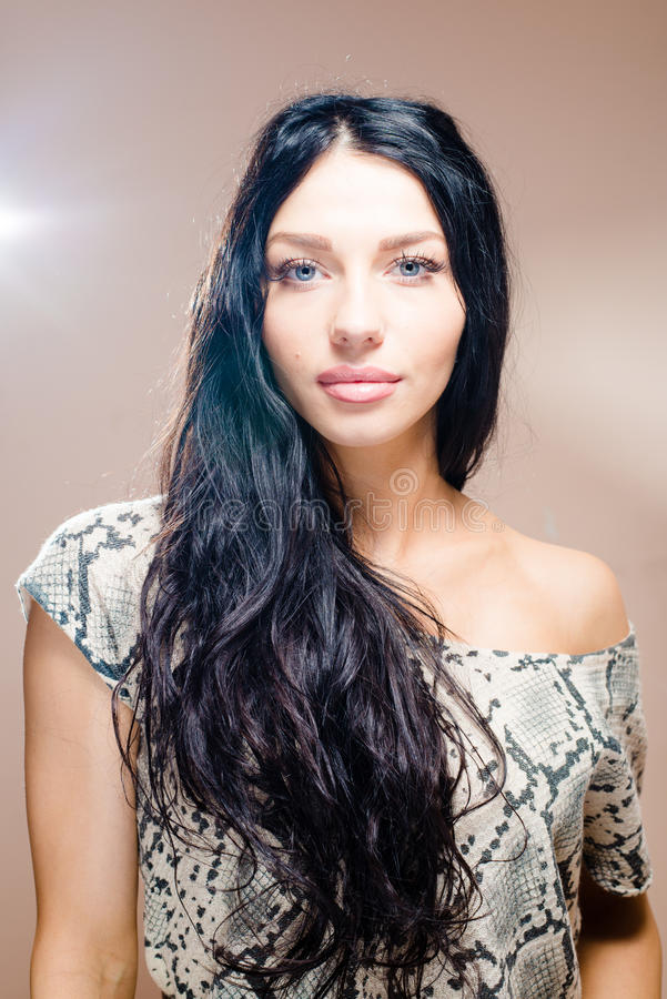 轻轻地微笑深色的美丽的妇女的图象有长的黑发蓝眼睛华美的嘴唇的鼓起一露出的肩膀 图库摄影