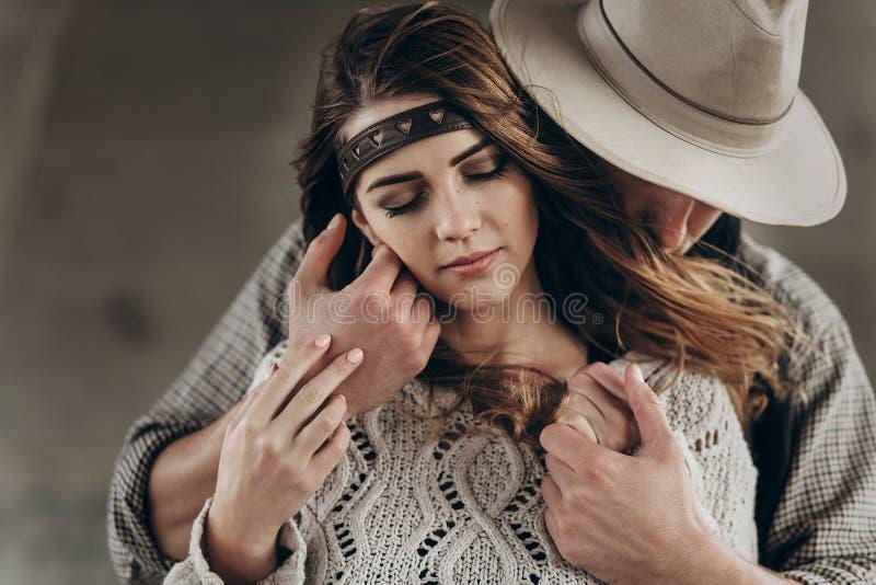 轻轻地拥抱时髦的行家的夫妇 帽子肉欲的touchi的人 免版税库存照片