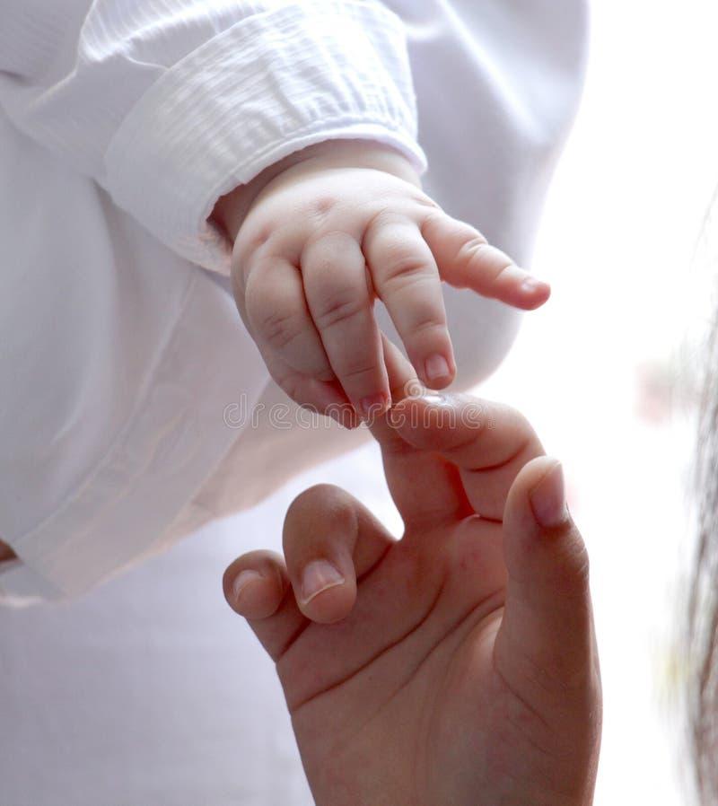 轻轻地握女孩手指的婴孩手 库存照片
