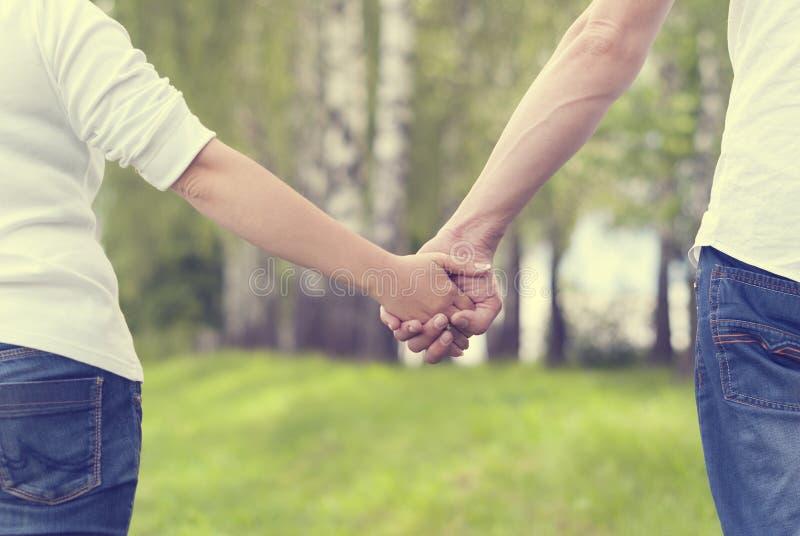 轻轻地握手的两个恋人一起 免版税图库摄影