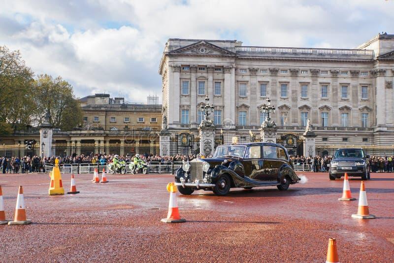 地方人民和游人招呼并且欢迎葡萄酒皇家汽车车事假白金汉宫 免版税库存图片