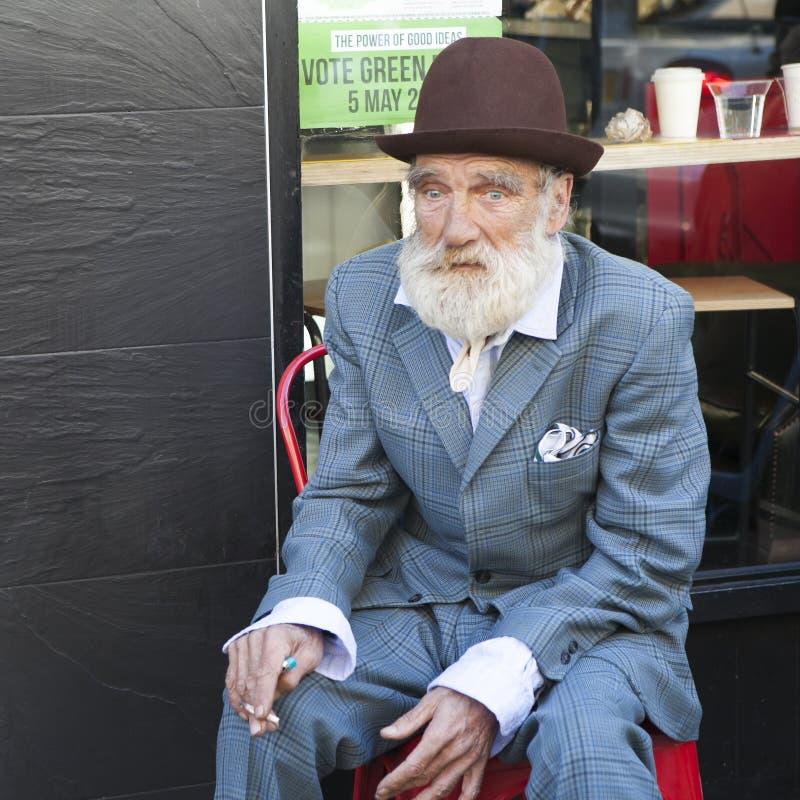 地方名人砖车道 抽在咖啡馆前面的时髦老人一根香烟 免版税库存照片