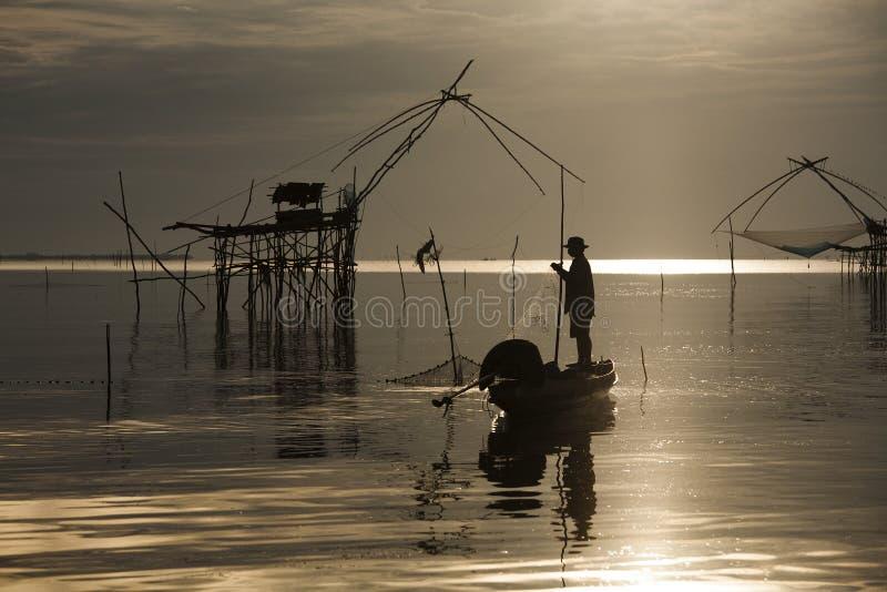 地方渔夫在沼泽地Talay Noi, Pattalung,泰国开始了他的工作清早,在金黄日出 免版税图库摄影