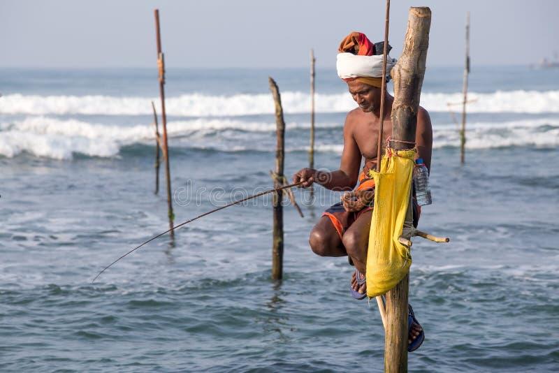 地方渔夫在独特的样式钓鱼在南斯里兰卡 免版税库存照片