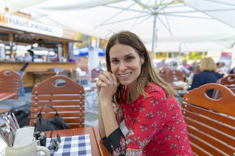 地方餐馆等待的食物的美丽的旅游妇女坐 免版税库存照片