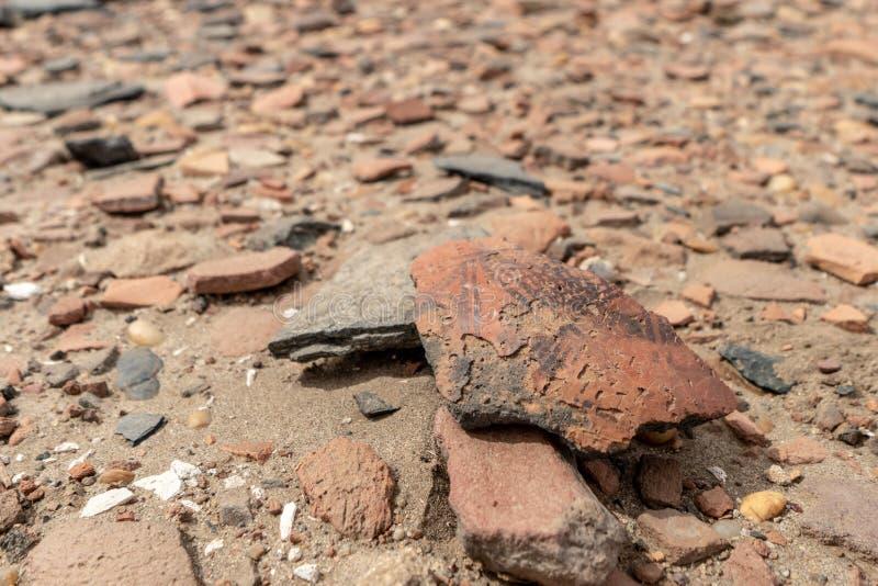 地板驱散与疏散瓦器片断thousends在一个考古学站点的在佐井海岛上在苏丹 免版税库存图片